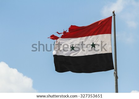 Homs, Syria, September 2013. Syria, September 2013. The flag of Syrian Arab Republic damaged by gunfire evolves in the sky. - stock photo