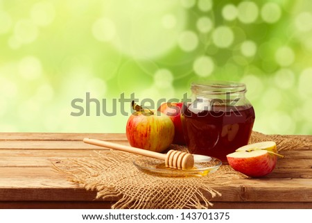 Honey and apples on wooden table over bokeh garden background - stock photo