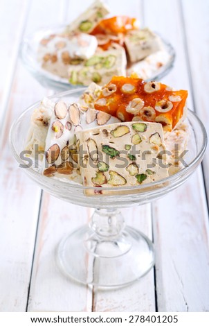 Honey and different sorts of nut nougat slices in a vase - stock photo
