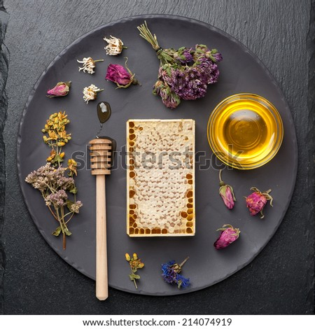 Honey and dried herbs on dark background  - stock photo