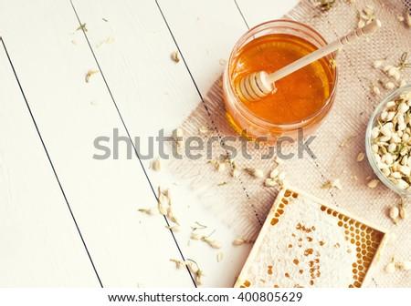 Honey and honeycomb with jasmine with copyspace - stock photo