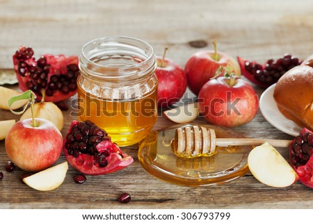 Honey, apple, pomegranate and hala, table set with traditional food for Jewish New Year Holiday, Rosh Hashana - stock photo