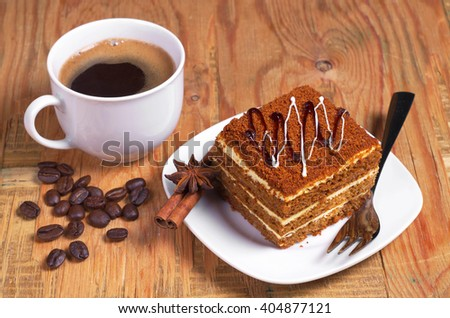 Honey cake and cup of coffee on old wooden table - stock photo