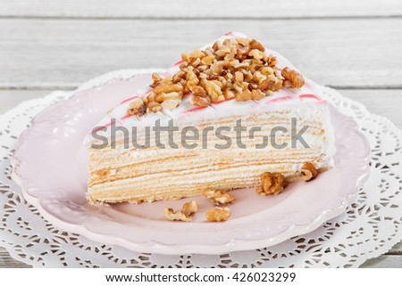 Honey cake with walnuts on plate, on a light wooden background. Selective focus - stock photo