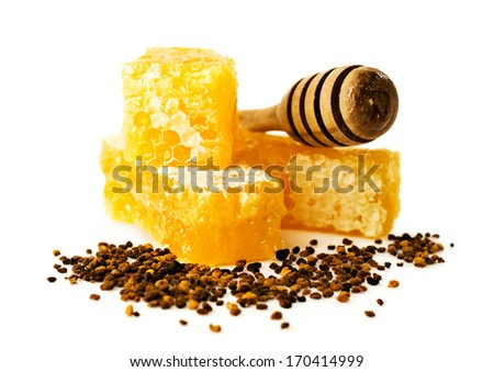 honey comb with a wooden dipper and pollen isolated on white - stock photo