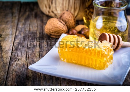 honey dipper and honeycomb, nuts in honey and nuts of various kinds, - stock photo