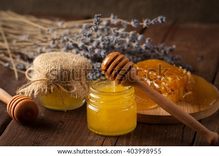 honey dipper and honeycomb with lavender, cinnamon and anise on wooden background. Healthy medical food concept. Natural products. - stock photo