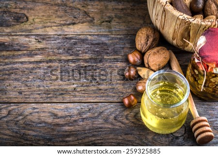honey dipper and nuts in honey, nuts of various kinds, - stock photo