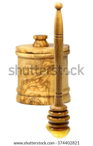 honey dipper and pot made of olive wood isolated on white background