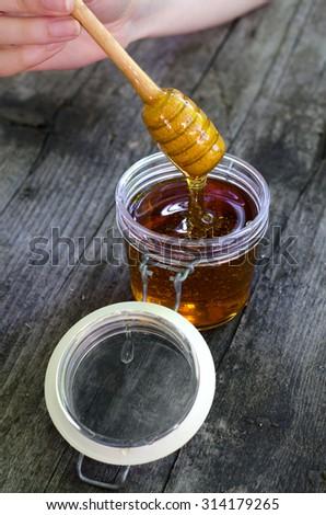 Honey dipper in glass jar full of honey on wooden table. - stock photo