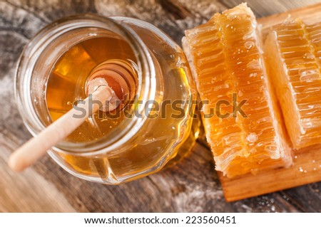 Honey dipper on the bee honeycomb background.  - stock photo