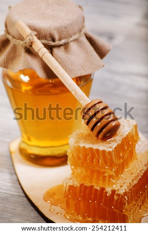 Honey dipper on the bee honeycomb background - stock photo