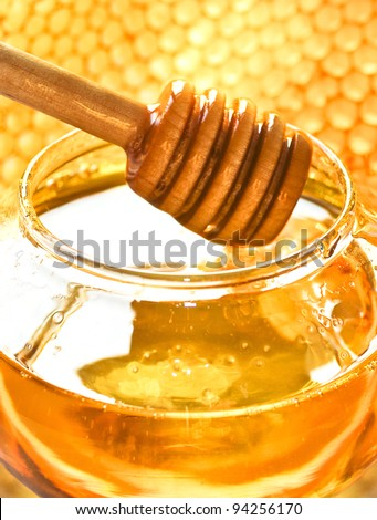 Honey dipper on the bee honeycomb background. Honey tidbit in glass jar and honeycombs wax. - stock photo