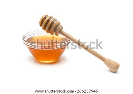 honey dipper with honey in a shell on white background - stock photo