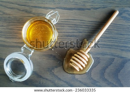 Honey dipper with honey on wood background. - stock photo