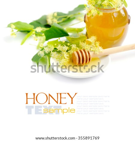 Honey dipper with honey with flowers of linden on white saucer - stock photo