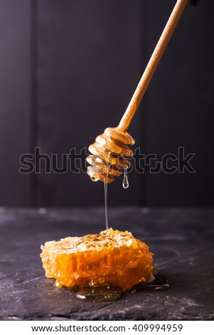 Honey drip and comb over black slate background - stock photo