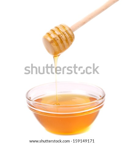 Honey dripping from a wooden dipper. Isolated on a white background.