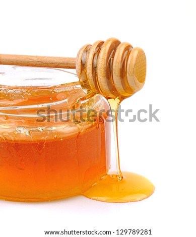 Honey dripping from a wooden honey dipper and jar on white background - stock photo