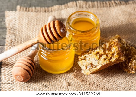 Honey dripping from a wooden honey dipper in a jar on wooden grey rustic background