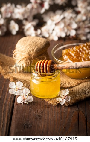 Honey dripping from a wooden honey dipper in a jar on wooden grey rustic background. Propolis and bee honey. Spring natural product concept.
