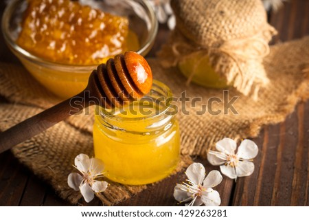 Honey dripping from a wooden honey dipper in a jar on wooden grey rustic background. Propolis and bee honey. Spring natural product concept. - stock photo