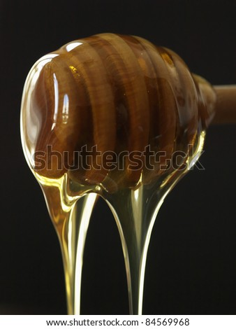 Honey dripping from a wooden honey spoon - stock photo