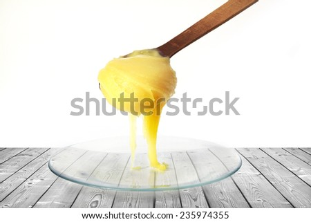 honey dripping from a wooden spoon isolated on white  - stock photo