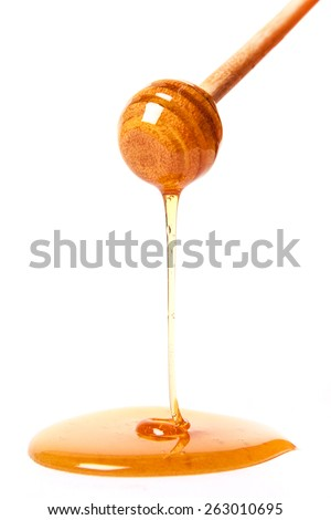 Honey dripping from wooden honey dipper - stock photo