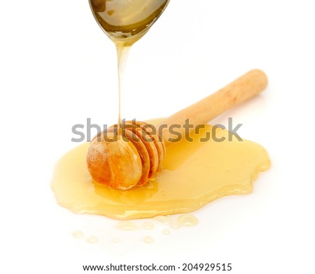 Honey dripping on wooden honey dipper on white background - stock photo