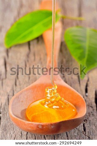 Honey falling on a spoon isolated on old wood - stock photo