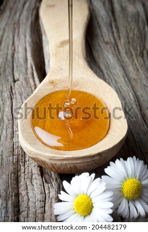 honey falling on rustic wooden scoop - stock photo