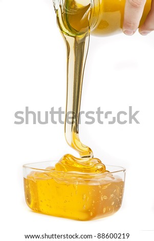Honey flowing from jar isolated on white background