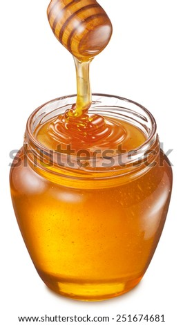 Honey flowing into glass jar. File contains clipping paths.  - stock photo