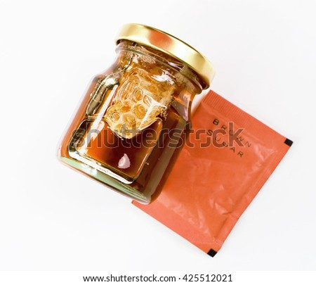 Honey from nature pollen flower in glass bottle and brown sugar bag isolated on white background. - stock photo