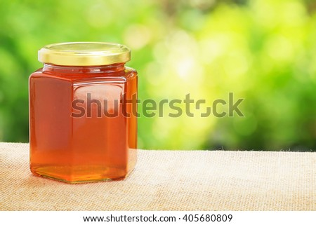 Honey from nature pollen flower  in glass bottle with green background. - stock photo