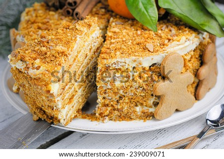 Honey gingerbread layered cake (medovik) decorated with gingerbread man cookies, mandarin oranges and spices. Close up - stock photo