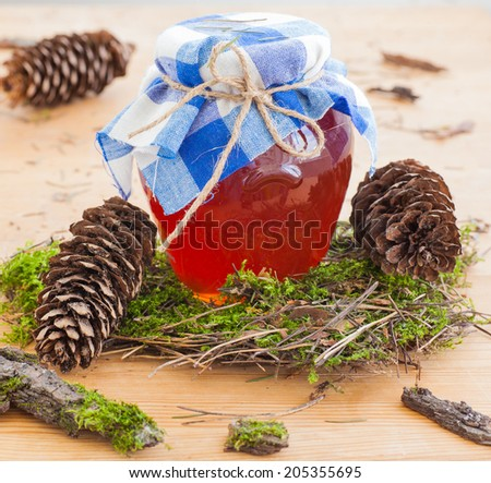 Honey glass pot with young pine on a wooden background - stock photo