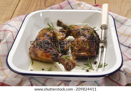 honey glazed chicken leg with olive oil, rosemary, meat fork in an blue and white enamel roasting dish - stock photo