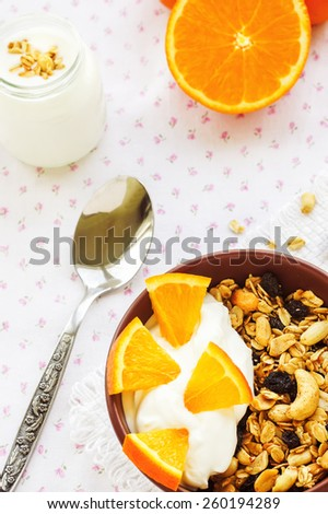 Honey glazed oatmeal, nut and coconut chips granola in a glass bowl with yogurt and oranges on a textile background - stock photo