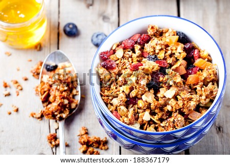 Honey glazed oatmeal, nut and flax seeds granola in a ceramic bowl with honey and fresh berries on a wooden background - stock photo