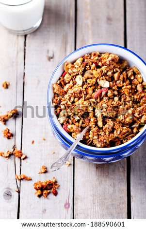 Honey glazed oatmeal, nut and flax seeds granola in a ceramic bowl with honey and yogurt  on a wooden background - stock photo