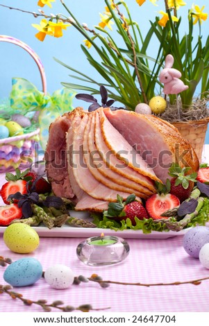 Honey ham on Easter table with eggs, flowers and decoration - stock photo