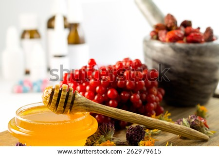 honey, herbs and medicines and pills in the background - stock photo