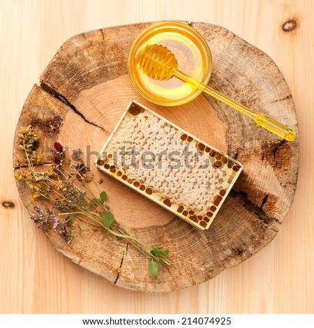 Honey, honey comb and dried herbs on wooden board  - stock photo