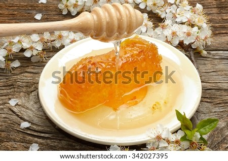 Honey, honeycomb and apricot flowers on wooden background - stock photo