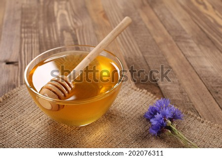honey in a glass bowl on a wooden boards background and burlap