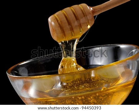 Honey in a glass cup with a dipper