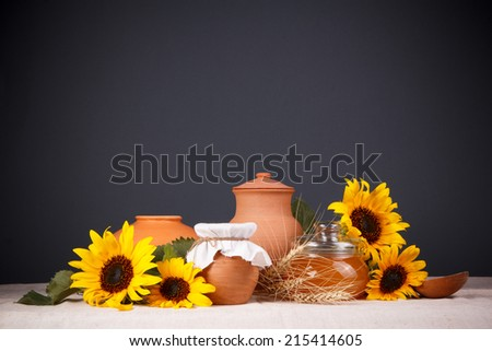 Honey in a glass jar and flower sunflower