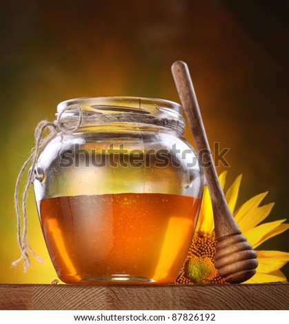 Honey in a glass jar and flower sunflower on a wooden table. - stock photo